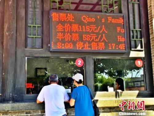 乔家年夜院景区卖票处旅客正正在购票 。  刘小白 摄
