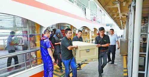 """工作人员将文物搬下客船。这两箱文物可以说是""""包船""""出行。"""