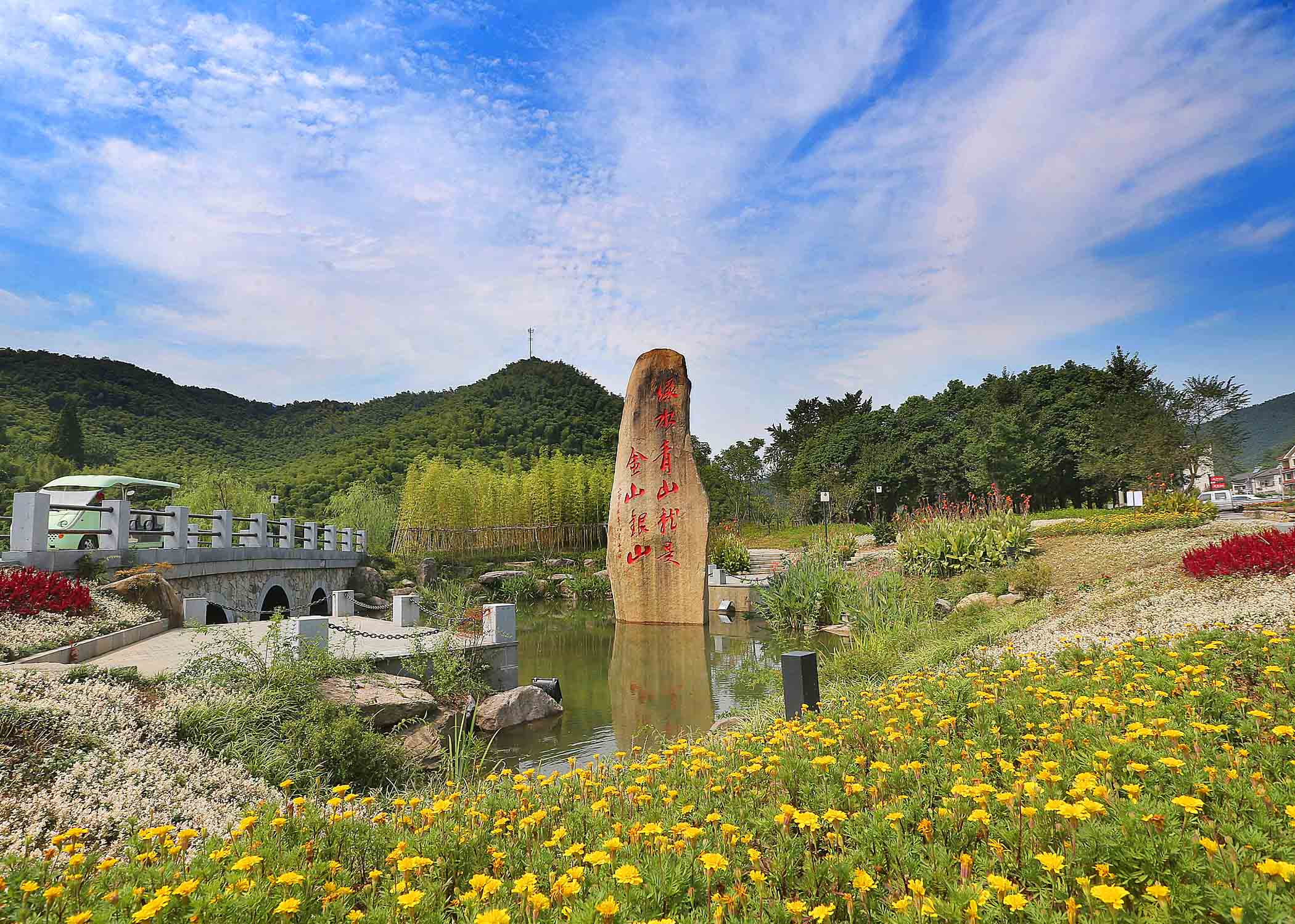 """在浙江安吉余村,铭刻着""""绿水青山就是金山银山""""的石碑就立在村头,无声地向游客""""讲述""""着余村的蜕变。 夏鹏飞摄"""