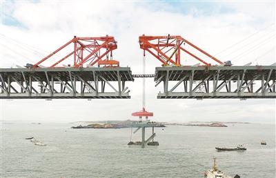 21日,平潭海峡公铁大桥鼓屿门航道桥的钢桁梁在吊装中供图/新华社