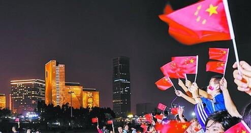 """观音山楼体艺术灯光秀上演,当""""祖国万岁""""""""我爱你中国""""等标语亮起时,人们挥舞国旗,祝福祖国。"""