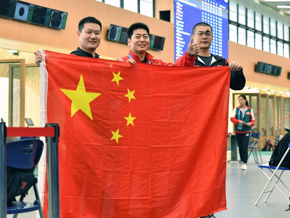 10月19日,中国队选手金泳德(中)、谢振翔(左)、姚兆楠庆祝夺冠。当日,在武汉举行的第七届世界军人运动会射击项目男子25米手枪军事速射团体比赛中,中国队夺得冠军。这也是中国代表团在本届军运会上的首枚金牌。新华社记者姜克红摄