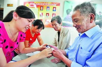 军门社区服务中心为该社区65岁以上老年人配发老年应急手机。 本报记者 林辉 摄