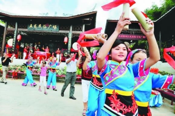 """在上杭县古田镇五龙村民俗广场,游客与五龙村民俗舞蹈队队员一起跳起欢快的""""节节高""""民俗舞蹈"""