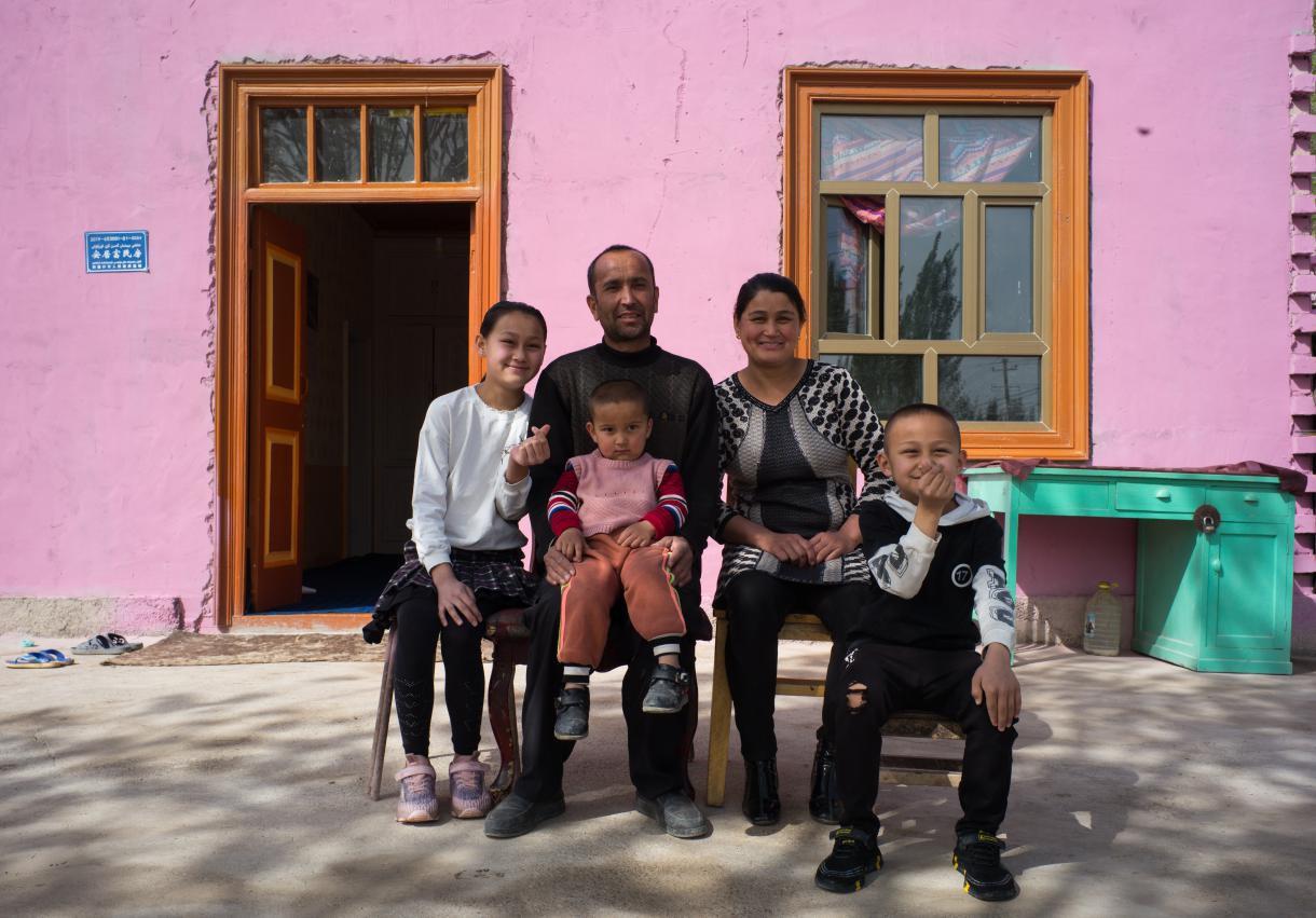 村民孜來汗·米吉提一家在新房前合影留念。