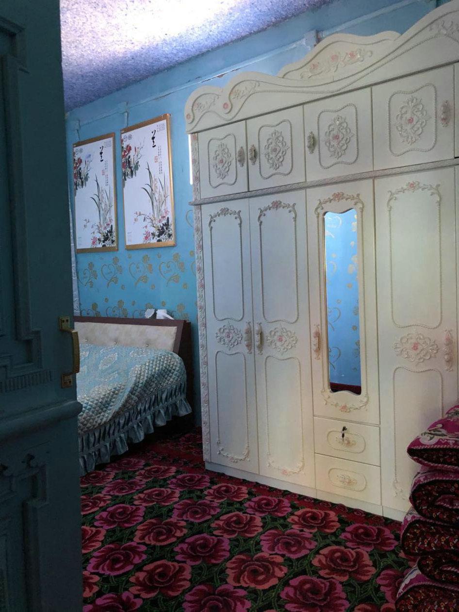 墩艾日克村一戶村民家中,床頭墻上的畫板為電熱板,日??僧斞b飾,冬季可發熱御寒。